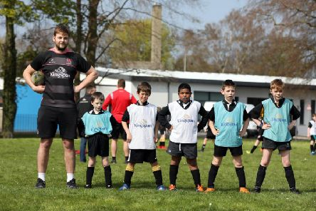 Edenderry Primary pupils size up to Ulster star Iain Henderson during a Kingspan Coaching Masterclass at the Portadown school