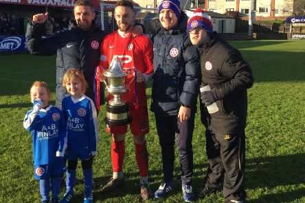 Hanover captain James Sergeant with the Bob Radcliffe Cup trophy in 2017. Also included are, back row from left, Steven Hyndes (manager), Dean Crowe (assistant manager) and Dean Wilson (team attendant), plus young fans Taylor Crowe (left) and Olly Hyndes.