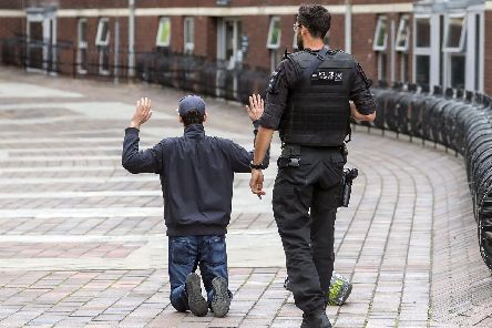 A Hampshire armed police officer detains a male near the Crown Court in Portsmouth, Hampshire. Picture: Steve Parsons/PA Wire