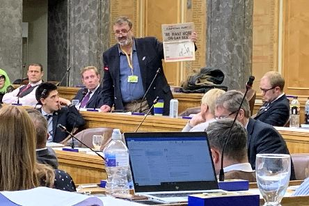 Cllr Lee Hunt holding up a copy of Capital Gay during full council. Picture: Ben Fishwick