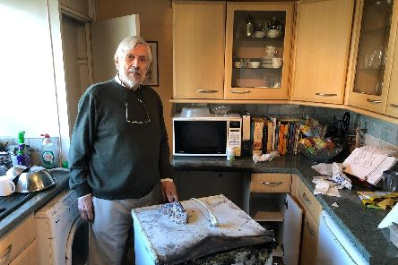 Paul Miller in his kitchen with the fire-damaged freezer 'Picture: Richard Lemmer