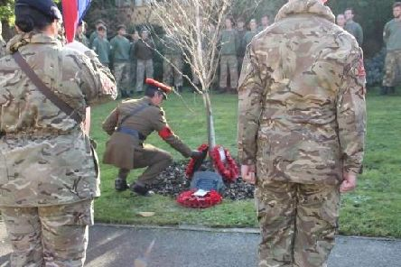 Major Dave Love lays a reef at the memorial to former student, Richard Hollington.