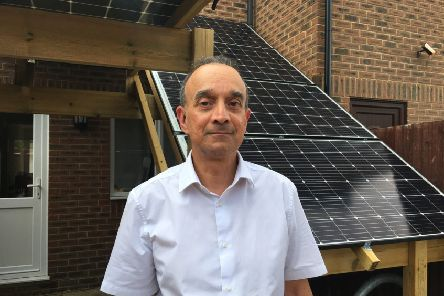 David Symons, 63, by the solar panel creation he made at his property in Little Pembrokes, Worthing