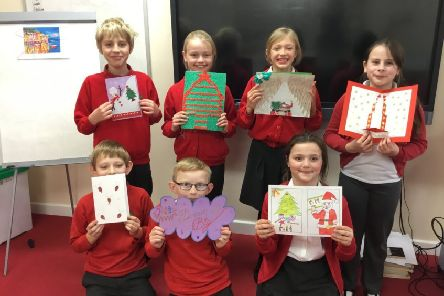 Children from Chestnut Street's 5GR class with cards they were sent from their partner schools in Lebanon.