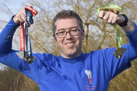 Cllr John Howard with his medals for completing the four marathons