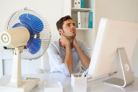 Casual businessman sitting at desk with electric fan in his office