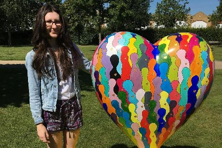 Catherine Spear with her sculpture Hearts of Gold in Crawley Memorial Gardens.