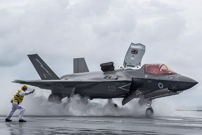 One of HMS Queen Elizabeth's flight deck officers Lieutenant Dave Robson launches the first ever UK F-35 from the supercarrier's black top. Photo: LPhot Kyle Heller.