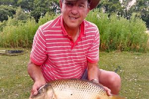 Steve Penticost with a carp, whose name has yet to be confirmed