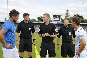 Referee Matt Russell speaks to Pompey skipper Gareth Evans and and Hawks captain  Wes Fogden