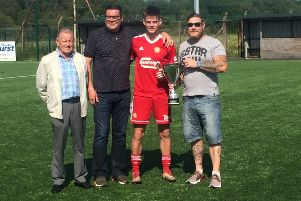Portadown captain Luke Wilson collects the George Richardson Memorial Cup at Tandragee Road. Representing the family of the former Ports kitman are, from left, Nat Richardson, Darren Richardson and Gareth Richardson.