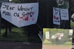 Some of the slogans erected near the Wrightbus factory in Ballymena at the weekend. Inset: an unidentified man removes all of the slogans by ripping them free.