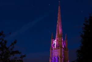 The spire of St James' Church, illuminated purple in recent years.