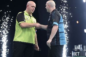 Rob Cross (right) shakes hands with opponent Michael van Gerwen at the 3Arena in Dublin tonight. Picture courtesy Michael Cooper/PDC