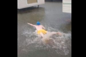 A still from the video where Alex 'swims' in the flood waters at Golden Palm Resort caravan park.