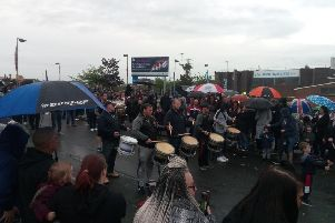 Bandsmen perform at Avoniel leisure centre, where the bonfire can be seen in the background on the far left