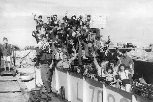 The landing craft has been loaded and the boys, and a few girls, are ready for the off. A Royal Marine supervises on the right.