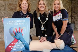 Lord Mayor of Armagh City, Banbridge and Craigavon Mealla Campbell learns how to administer CPR by Investing for Health Officers Elaine Devlin and Cathy Devlin