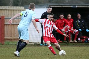 Easington Sports' Reece Bayliss gets in a cross despite the atentions of and Cirencester Town's Sam Farr