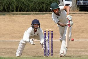Buckingham II batsman Matthew Thatcher plays his shot as Banbury wicket keeper Chloe Hill gets set