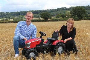Tysoe author Beki Benjamin, right, has written a children's book about a boy and his tractor. She is pictured with illustrator Josh Welsby, left, and a toy tractor she is giving away in a prize draw. NNL-181018-172439001