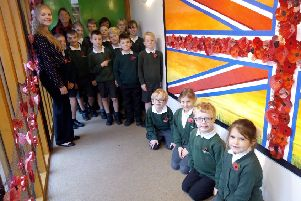 Teachers Mrs Messer (rear) and Ms Upstone with Year 4 students and the Armistice poppy memorial NNL-181113-094846001