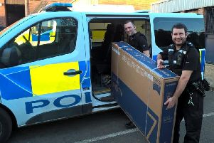 Police officers with the seized TV. Photo: Thames Valley Police