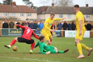 Kettering Town's Dan Holman tries to take advantage of Banbury United keeper Jack Harding being on the ground as Charlie Wise and Lee Henderson look on. Photo: Peter Short