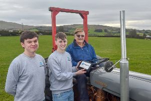 St. Mary's Grammar School pupils John McElhone and Micheal McLaughlin demonstrate their CropSafe app to Micheal's grandfather, Mickey Joe McGuigan, on his farm in Draperstown.