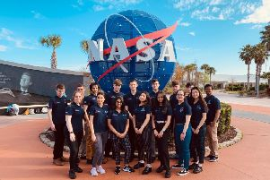 The students pose with the iconic NASA logo