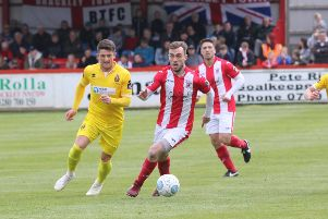 Brackley Town's Shane Byrne gets away from Spennymoor Town's Rob Ramshaw. Photo: Steve Prouse