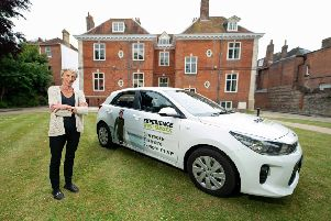 Louise Goldsmith, council Leader, sees one of new vehicle-branding designs, in front of historic Edes House