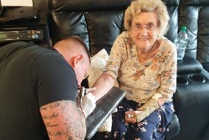 Tattoo artist Matty Gardner inks the tattoo onto the wrist of Hilda West