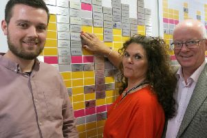 Ben, Sarah and David Long pictured next to Brain Tumour Research's wall of hope