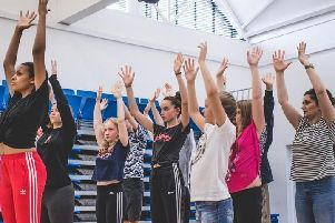 The group with their hands in the air during Now and Then Theatre's physical theatre workshop at the Royal Latin School