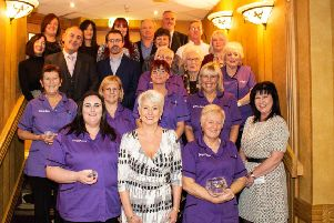 Long service awards have been made to staff of Extra Care. They are joined by UTV presenter Pamela Ballantine.