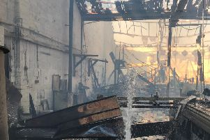 A fire-fighters hose-reel jet is seen powering water into Mr Seamark's workshop in Wellingborough after the fire on July 5.