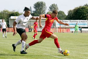 Banbury United's Charlie Hawtin comes away with the ball from Royston Town's Adam Murray