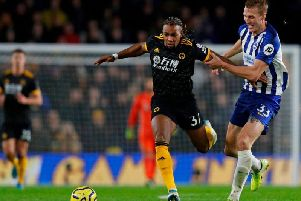 Brighton and Hove Albion defender Dan Burn tussles with Adama Traore