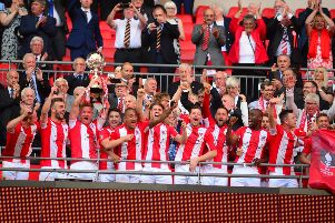The Brackley Town players receive their medals and the Buildbase FA Trophy at Wembley