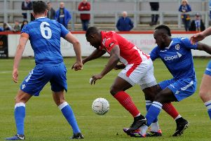 Brackley Town top scorer Lee Ndlovu is crowded out against Guiseley. Photo: Jake McNulty