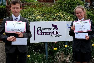 Ben Joyce and Chloe Pool outside George Grenville Academy with their thank you certificates from the Florence Nightingale Hospice