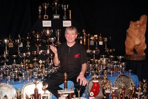 Motorcycling legend Joey Dunlop pictured with some of the vast haul of silverware he won during his illustrious career. The Ballymoney man was tragically killed in a crash in Estonia in 2000.