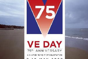 Foreground, VE Day logo. Background, Omaha Beach