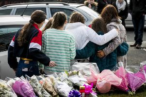 A group of young teenage girls escorted by their families leave floral tributes at the entrance of The Greenvale Hotel in Cookstown Co. Tyrone were three teenagers died on the evening on St Patrick's