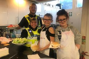 PCSOs from Skegness help Skegness Youth Club members dish up some burgers at a special engagement evening.