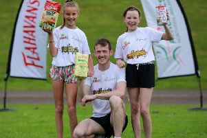 Hannah O'Toole from Linn Primary School help launch this year's Flahavan's Athletics NI Primary School Cross Country League with  Para World Championship finalist and Flahavan's Ambassador, James Hamilton and Abigail Curran from Stranmillis PS