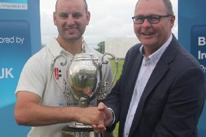 Brigade captain Andy Britton receives the NW Senior Cup trophy from Ian Stone (Bank of Ireland).