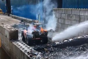 A digger takes fiery waste from the building.