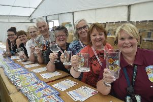 Peterborough Beer Festival 2019 at the Embankment.  Beer festival volunteers  handing out glasses. EMN-190820-175931009